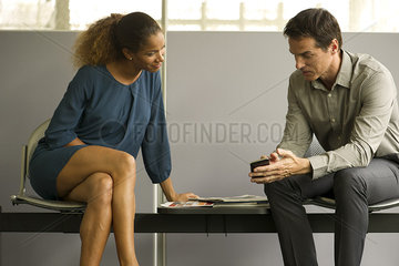 Professionals chatting in waiting room  man showing woman smartphone