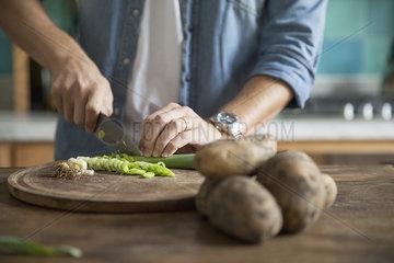 Man cutting spring onion in kitchen