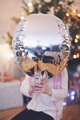 Child with face obscured by silver balloon