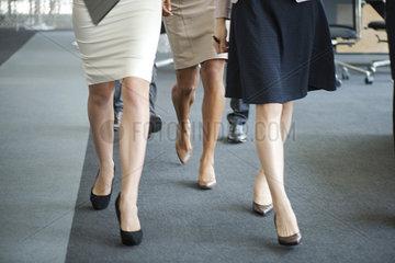 Businesswomen walking in office  low section
