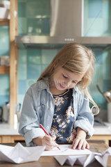 Little girl drawing in kitchen  portrait