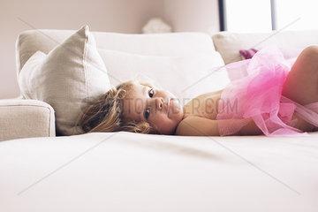 Little girl lying down on sofa in tutu