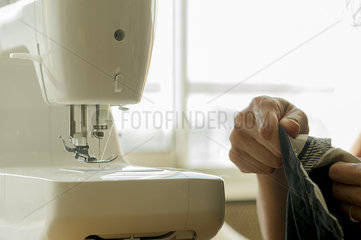 Woman using sewing machine  cropped