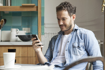 Man reading news on smartphone while having breakfast