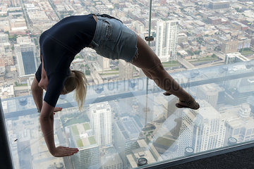 Woman doing backbend in glass-bottomed overservation deck at Willis Tower  Chicago  Illinois  USA