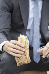 Businessman holding sandwich  cropped