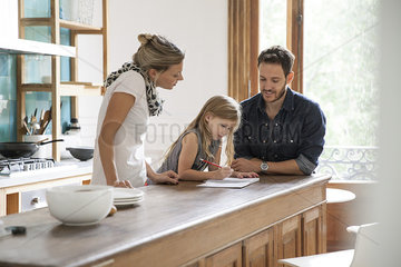Parents helping young daughter with lessons