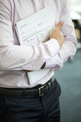 Businessman holding contract against chest  cropped