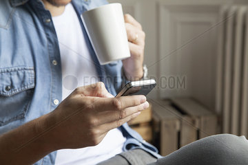 Man catching up with emails while having morning coffee