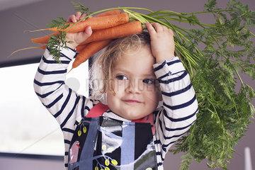 Little girl holding fresh carrots over her head  portrait