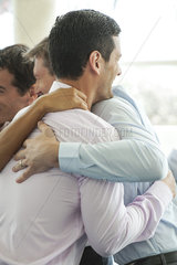 Businessmen hugging in celebration over good news