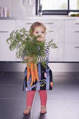Little girl holding fresh carrots
