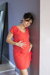 Pregnant woman leaning against wall with hands on stomach  portrait