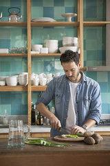 Man cutting ingredients in kitchen