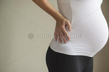 Pregnant woman massaging lower back