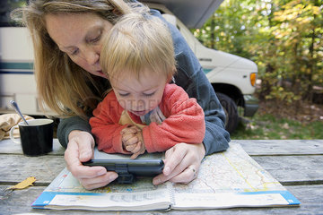 Mother holding child on lap while using atlas and GPS to plan road trip
