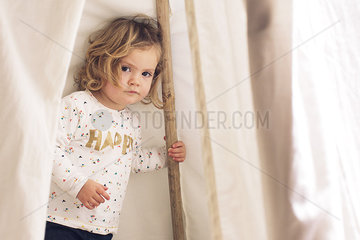 Little girl playing in tent  portrait