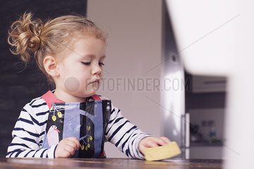Little girl wiping table with spong