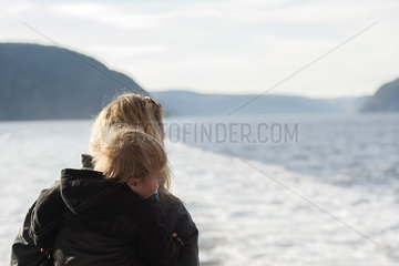 Mother and young son looking at tranquil lake view