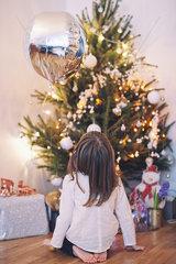 Girl sitting on floor gazing up at Christmas tree