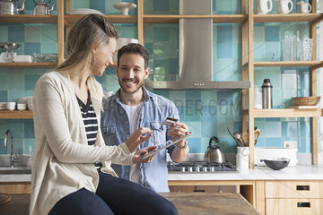 Couple using digital tablet in kitchen