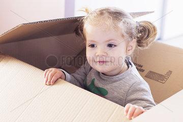 Little girl playing in cardboard box
