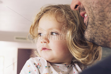 Little girl with father  looking away in interest