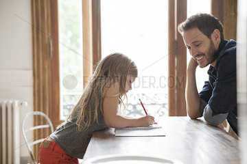 Father helping daughter practice writing