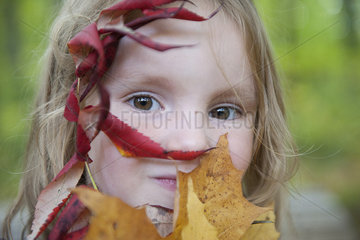 Girl holding autumn leaves in front of her face  portrait
