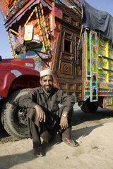 Pakistani Truckdriver in front of his decorated truck