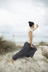 Woman practicing tai chi chuan on beach  side view