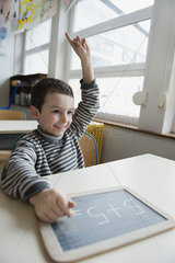 Boy sitting at desk with chalkboard  hand raised