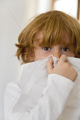 Boy blowing nose on tissue