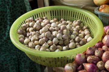 Basket of shallots on market stall