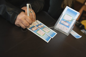 Hands of woman filling out lottery tockets