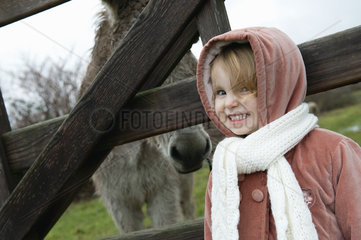 Little girl posing for picture with donkey behind fence  portrait