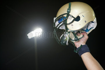 Football player holding up helmet in victory  cropped