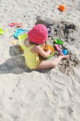 Kleines Maedchen mit Strandspielzeug