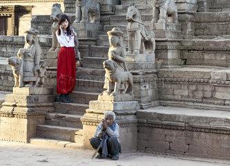 Chinesisches Model und nepalesischer Bettler bei Werbeaufnahmen