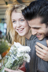 Young woman pleased after receiving flower bouquet from boyfriend