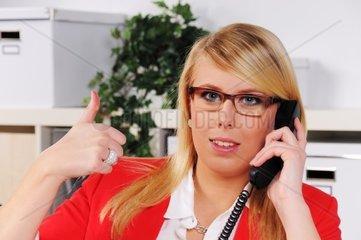 junge Frau mit gehobenen Daumen beim Telefonieren im Buero