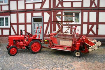Rote Trecker vor eine Fachwerkhaus in der Schwalm.