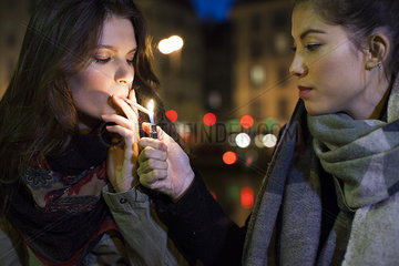 Woman lighting friend's cigarette