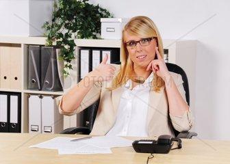 junge Frau sitzt mit gehobenem Daumen im Buero am Schreibtisch