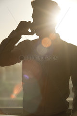 Man talking on cell phone  silhouetted by sun shining through window