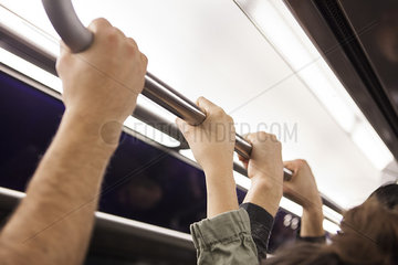 Communters on subway holding grab handle  close-up
