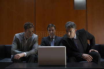 Business associates sitting side by side on sofa looking at laptop computer in disbelief