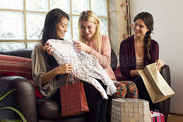 Young woman showing friends contents of shopping bag