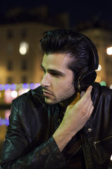 Young man outdoors at night listening to music with headphones