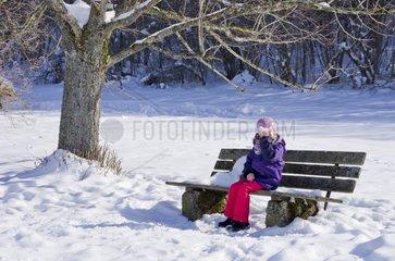 Kleines Maedchen sitzt unter einem Baum auf einer Bank in winterlich verschneiter Umgebung und haelt vereisten Schneeklumpen wie eine Maske vors Gesicht